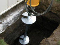 Installing a helical pier system in the earth around a foundation in Bridgeton