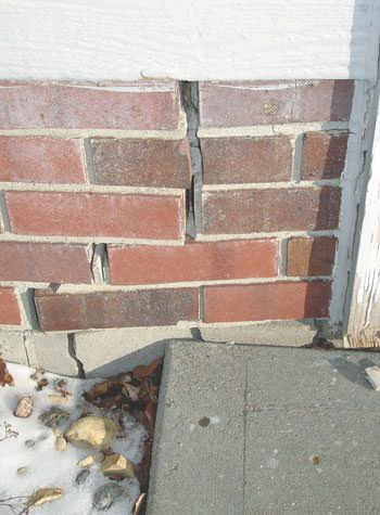 Severe street creep damage to a garage wall outside a Minotola home